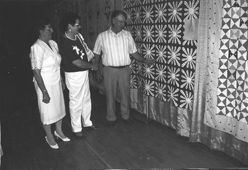 Mr. and Mrs. Claude Lenzmeier and Matheal Schneider with St. Hubert's name quilt.