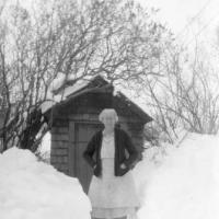 Blanch (Sampson) Lawson standing by out-house in winter - circa unknown